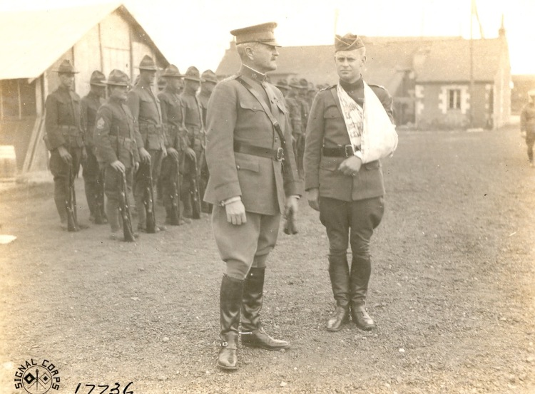 Pershing standing w injured soldier