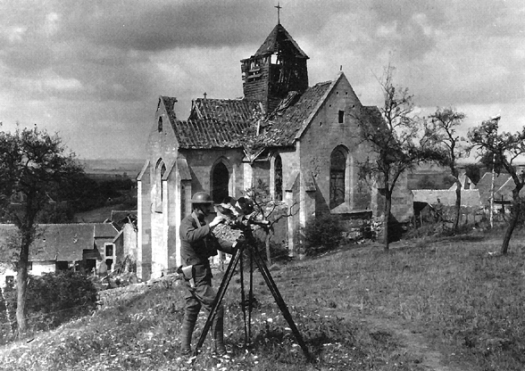 SIGNAL CORPS PHOTOGRAPHER OPERATES A CAMOUFLAGED CAMERA IN FRANCE