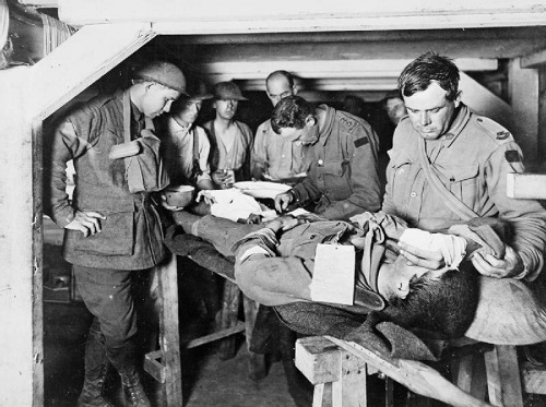 An Australian Medical Officer attends a wounded man at an Advanced Dressing Station during the Third Battle of Ypres in 1917. Imperial War Museum copyright image E(AUS)714.