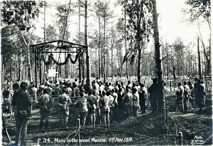 Mass in the wood Monaco. 1st Nov. 1917 a large group of soldiers stands in a forest facing a makeshift altar built between the trees barned wire and crosses