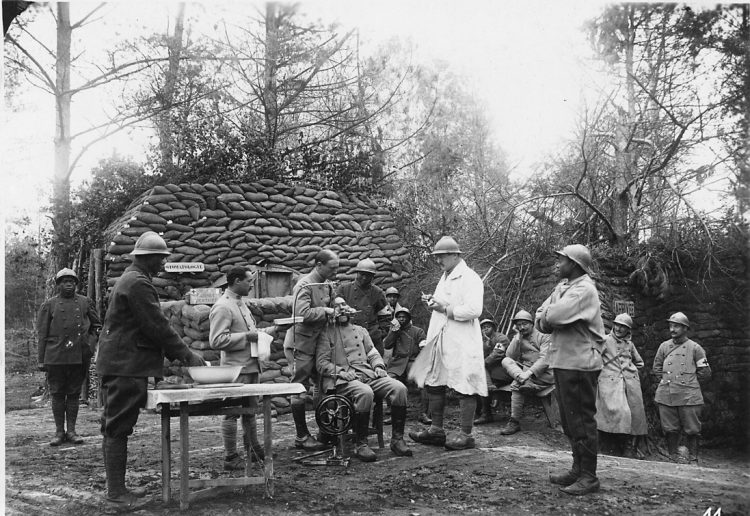 Monaco near Chemin des Dames Sept. 1917 A man sits on a chair outdoors while the man standing behind him places two dental tools in his open mouth. A dental machine powered by